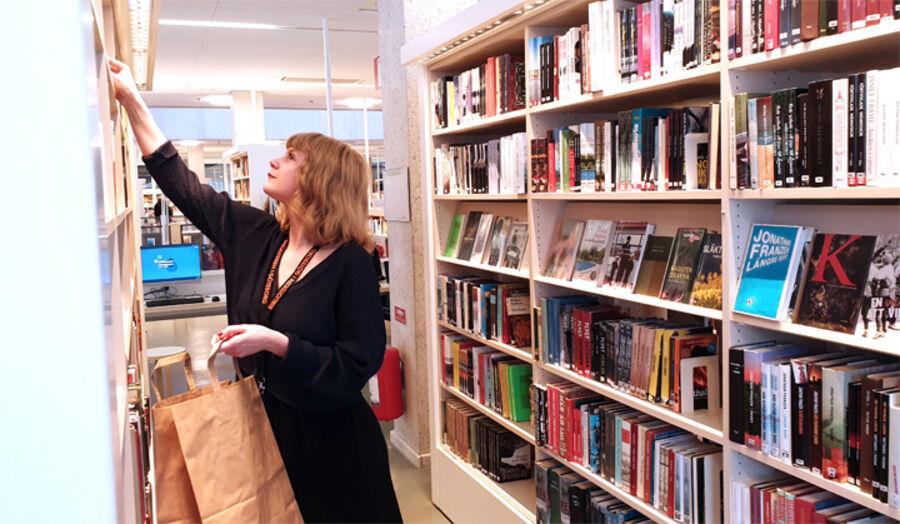 Bibliotekarie Maria Olsson packar en kasse till en låntagare.